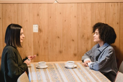 Side view of young friends with dark hair talking while having breakfast with cups of tea at table