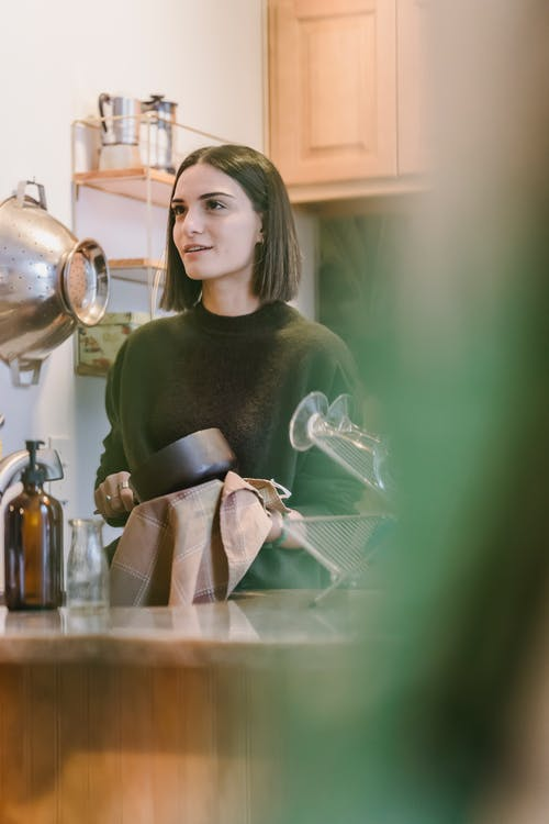 Женщина в зеленой рубашке с длинным рукавом с серебряным чайником
