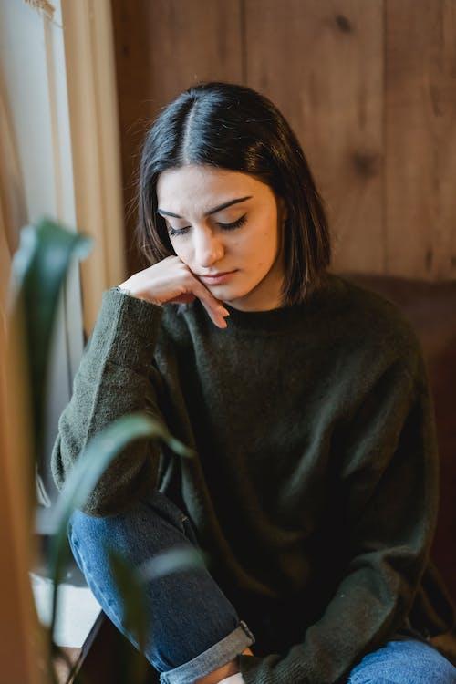 Wanita Dengan Sweater Abu Abu Duduk Di Kursi