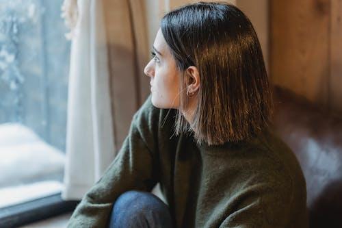 Thoughtful woman sitting on windowsill in solitude