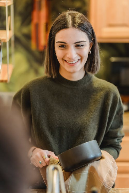 Positive female with toothy smile cleaning pan with towel while listening to friend in cafe
