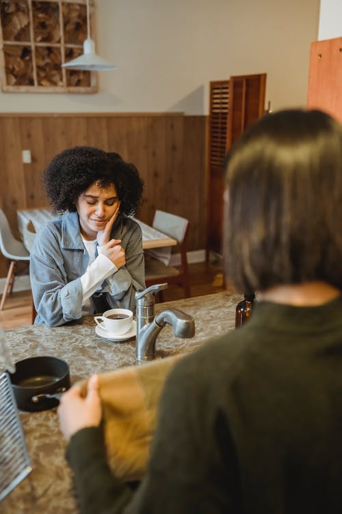 Desperate black woman having coffee with friend
