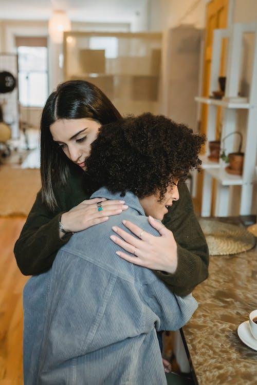 Young woman hugging upset black girlfriend