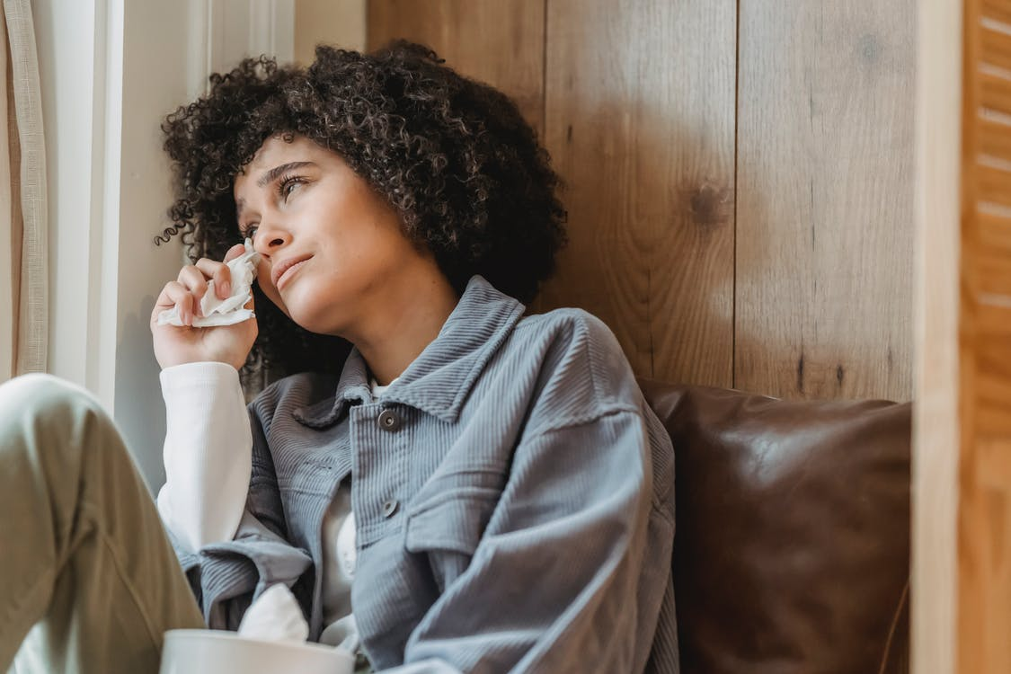 Desperate African American female with curly hair wiping face with tissue while crying from sadness on windowsill and looking away