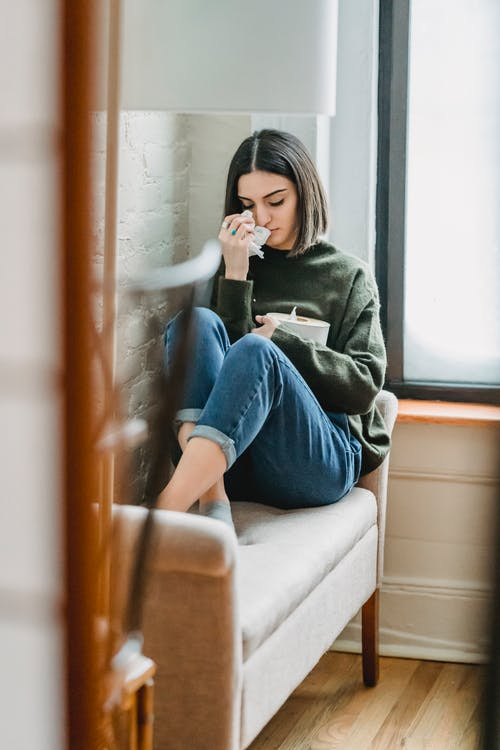 Woman in Green Sweater and Blue Denim Jeans Sitting on White Couch