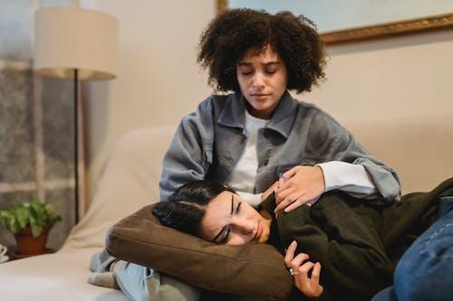 Young black woman cuddling crying female friend lying on sofa