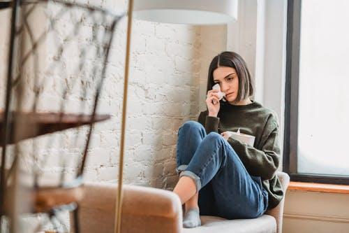 Woman in Gray Sweater and Blue Denim Jeans Sitting on Brown Leather Armchair