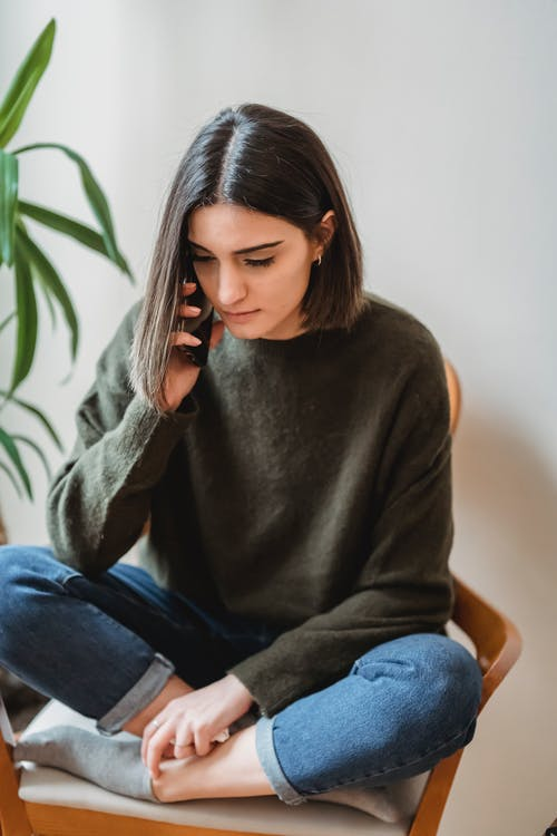 Serious young ethnic female millennial talking on smartphone sitting on chair