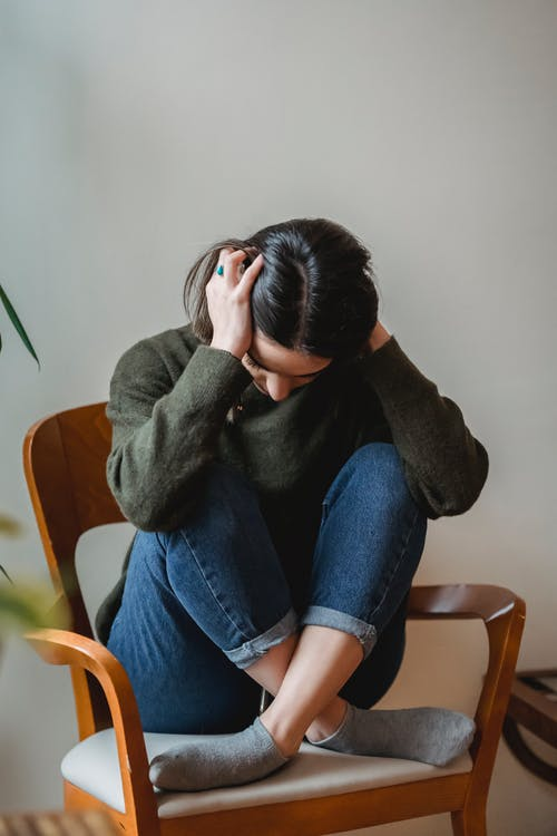 Anxious young woman cover wing ears with hands sitting on chair