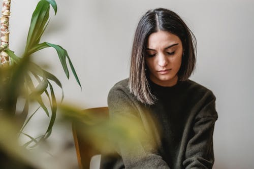 Woman in Black Turtleneck Sweater Sitting on Brown Wooden Chair