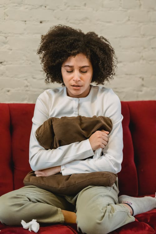 Full body of sorrowful young African American female millennial with curly hair embracing pillow and crying while sitting on sofa at home
