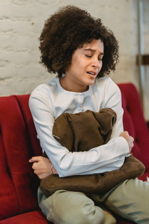 Depressed African American female in casual wear with closed eyes crying while sitting on comfortable sofa in living room at home