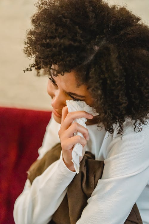 Depressed African American female with black curly hair wiping tears with tissue while sitting on sofa with cushion at home