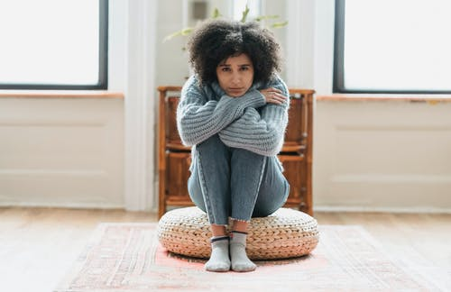 Full body of sad African American female looking at camera while sitting on rattan mat in light room at home