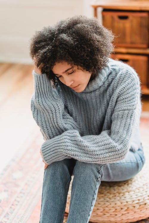 Sad black woman sitting in room
