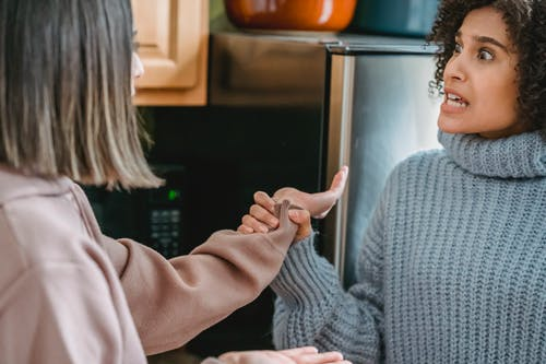 Angry African American female in casual wear shouting and grabbing hand of anonymous female while fighting and looking at each other in kitchen
