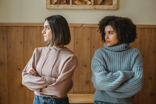 站在灰色毛衣的女人旁邊的女人