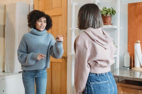 Frau Im Grauen Pullover Und In Den Blauen Jeans, Die Nahe Der Braunen Holztür Stehen