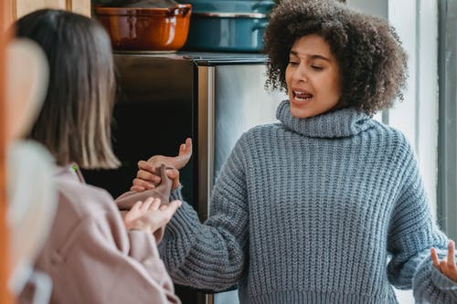 Furious African American female screaming and grabbing hand of faceless woman while having fight in modern light kitchen at home