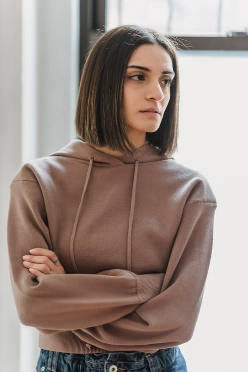 Disappointed female looking away with thoughtful look while standing with arms crossed near big window in light room at home