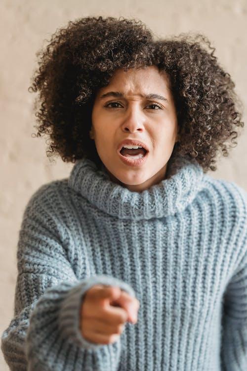 Angry black woman pointing at camera
