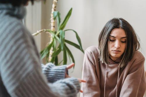 Женщина в коричневом худи сидит на сером диване