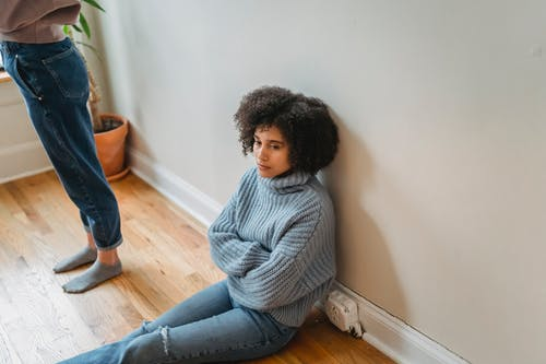 Mujer En Camisa De Manga Larga A Rayas Grises Y Blancas Y Pantalones Vaqueros Azules Sentados En El Piso