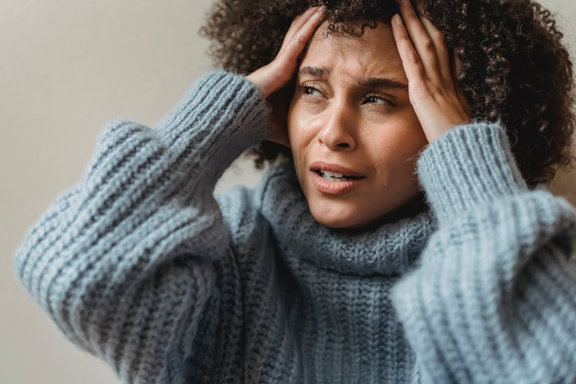 Worried African American female with brown curly hair crying and touching head against light wall