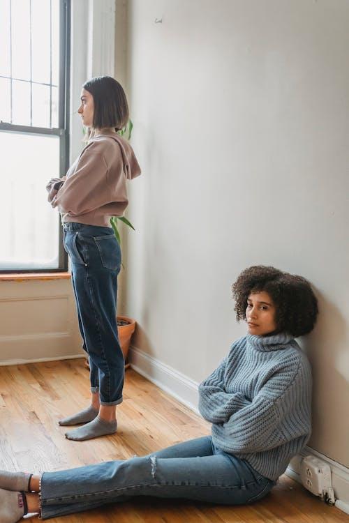 흰색과 검은 색 줄무늬 긴 소매 셔츠와 흰색 옆에 서있는 파란색 데님 청바지에 소녀