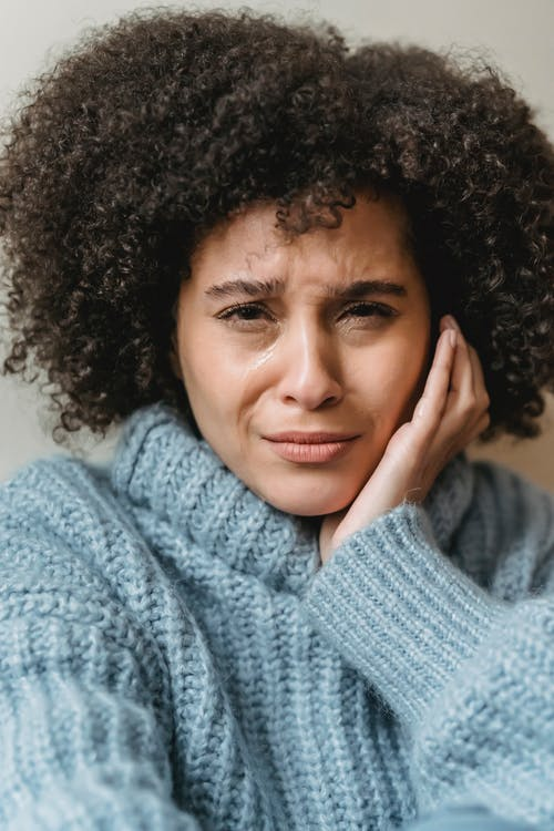 Sad black woman in sweater crying with hand on face