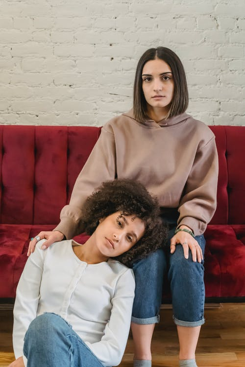 Young serious multiracial female friends sitting in light living room with lady laying head on laps of female on sofa near white brick wall and looking at camera