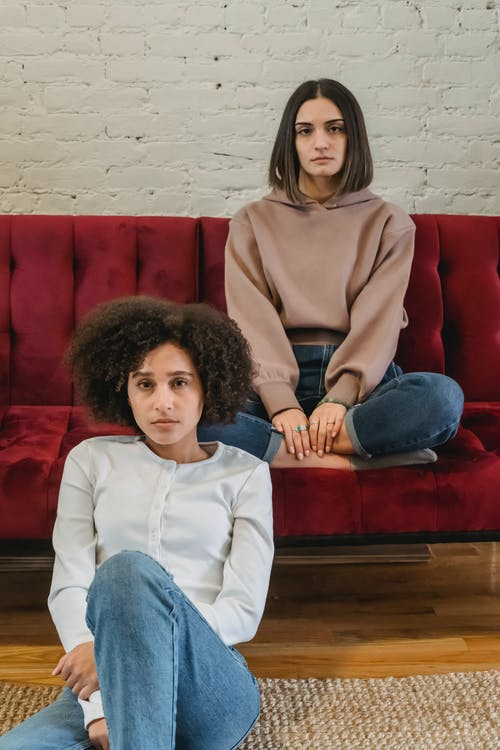Young serious multiethnic female friends sitting in bright room with sofa near white brick wall and looking at camera