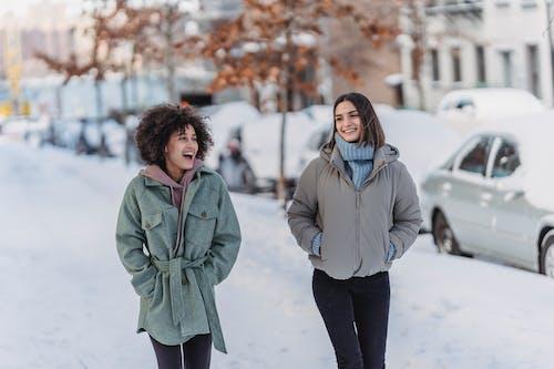 Positive multiethnic girlfriends walking on snowy street