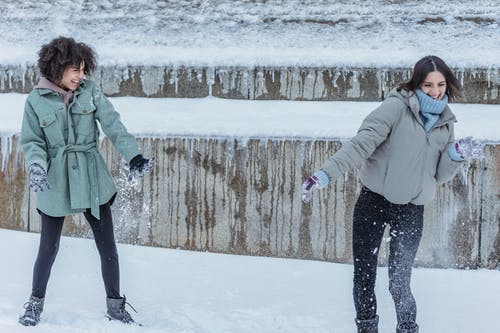 Delighted multiethnic girlfriends in outerwear laughing widely while having fun together in winter snowy park
