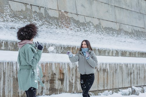 Cheerful woman playing snowball fight with friend