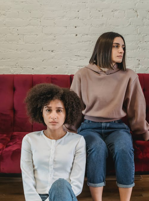 Upset woman sitting on sofa near black friend with disappointed face while having conflict and misunderstanding