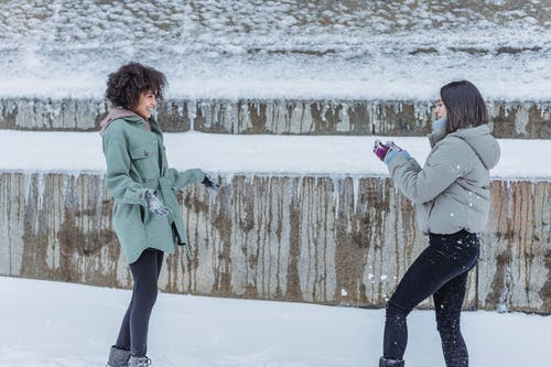 Happy diverse women playing with snow in winter park