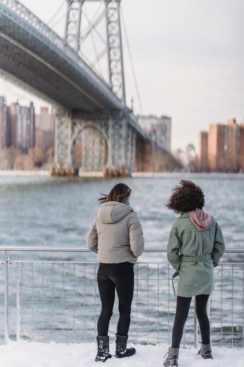 Full body of unrecognizable girlfriends with hands in pockets standing near railing on waterfront against bridge