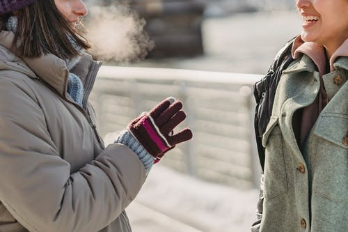 Crop joyful young female friends in warm clothes chatting merrily while standing on city embankment on freezing winter day