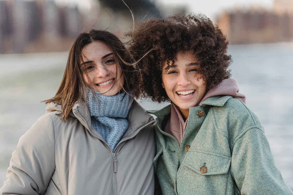 Attractive joyful multiethnic female friends wearing warm clothes standing together on city street and looking at camera happily on cold winter day