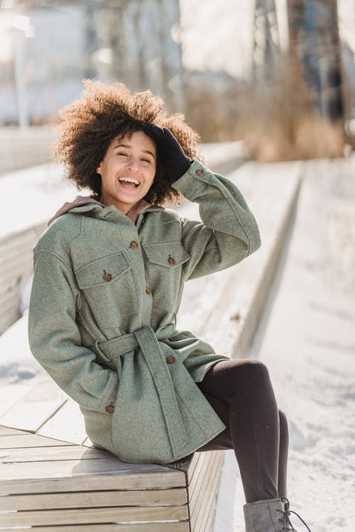 Happy young ethnic female wearing warm coat touching curly hair and looking at camera while sitting on wooden bench in snowy park on cold winter day