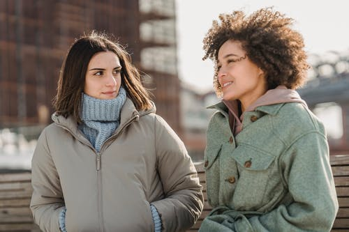 Glad young multiracial female friends in warm clothes chatting and strolling together on city street on cold freezing day