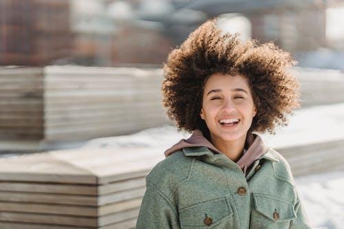Joyful ethnic woman standing in snowy city park