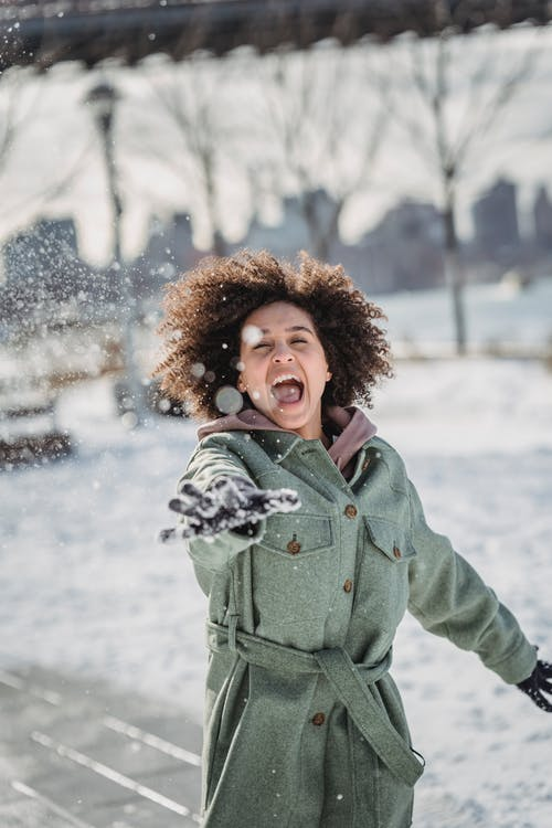 Expressive ethnic woman throwing snowball in winter park
