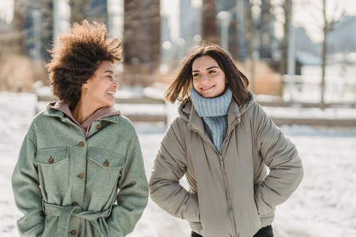 Carefree young multiethnic female friends in warm clothes walking together with hands in pockets on snowy city street and chatting