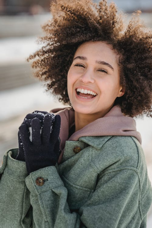 Joyful ethnic woman with snowball standing in winter park