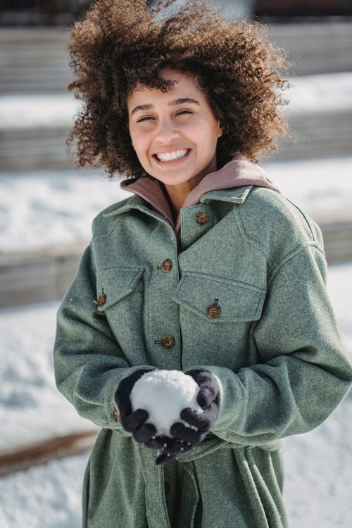 Smiling young ethnic female in warm coat and gloves holding snowball and looking at camera while spending sunny winter day in park