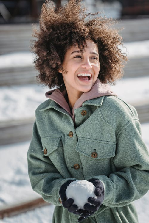 Excited ethnic woman with snowball in winter park