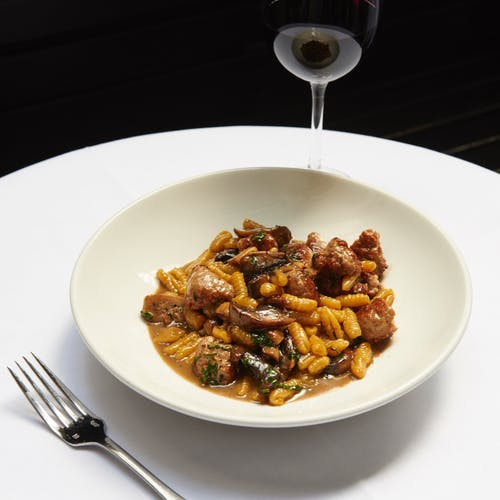 From above of palatable dish with gnocchi pasta and meat in sauce served in white ceramic plate and placed on round table with glass of wine in restaurant