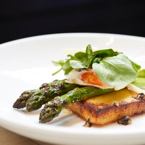 Delicious toast with asparagus and poached egg served with herbs on plate
